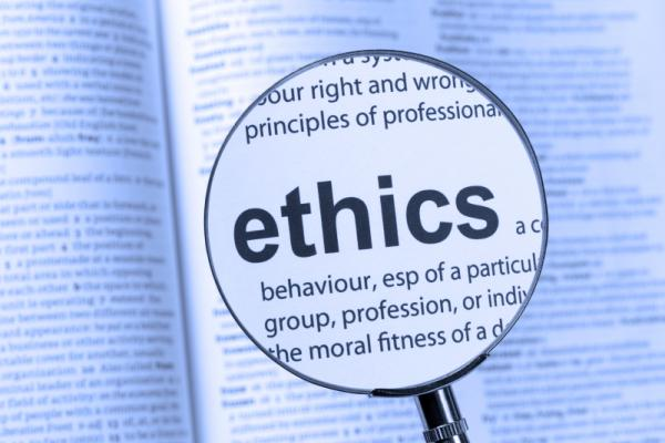 A magnifying glass focusing on the word Ethics in a dictionary.