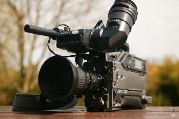 A professional video camera placed on a table, with trees in the background